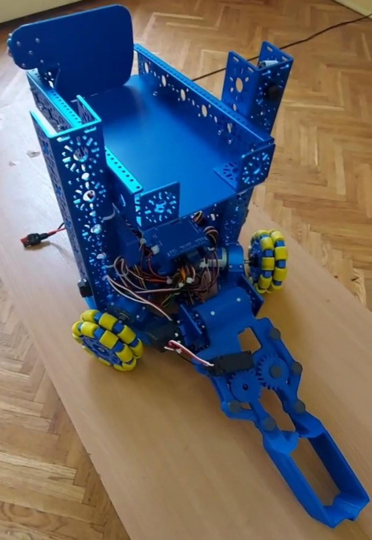 Вид на собранного робота с соревнований. Захватом спереди схватываем контейнер и поднимаем наверх. Сверху расположен бункер для временного хранения отходов по пути в центр переработки